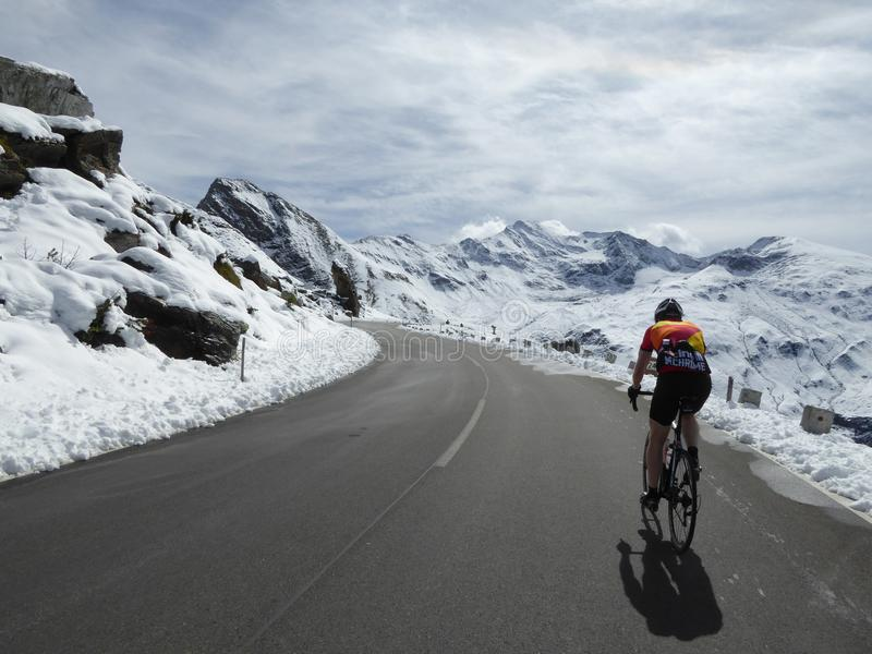 Cyclist in snow covered mountains royalty free stock photos