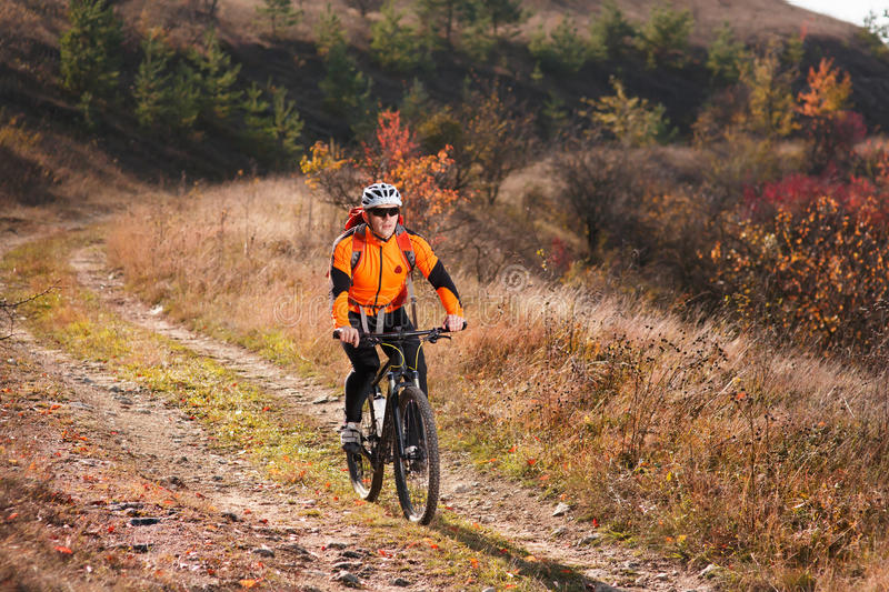 Cyclist in the sportive orange jacket riding a mountain bike along the trail in the countryside at sunset. Yclist in the sportive orange jacket riding a royalty free stock photo
