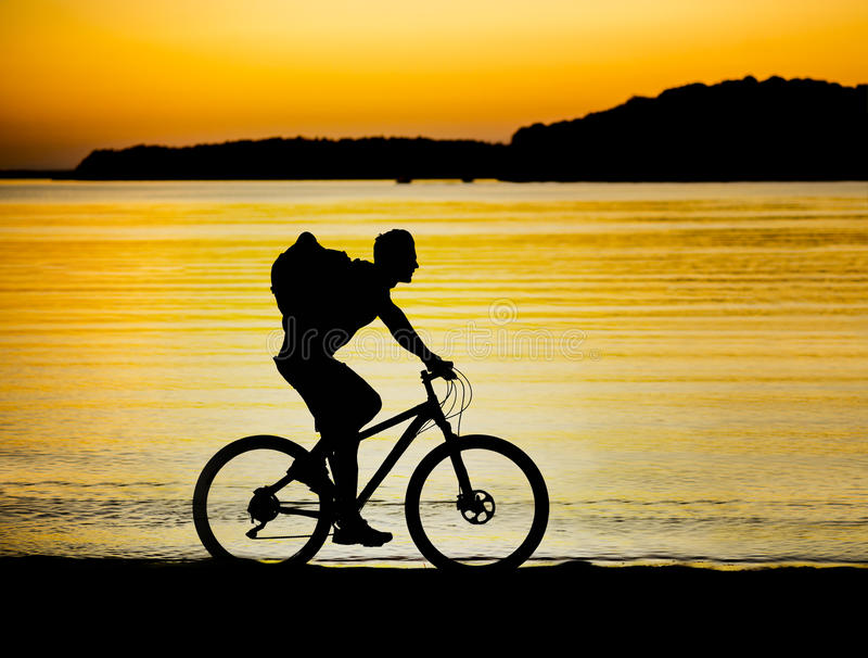 Cyclist at sunset stock photo