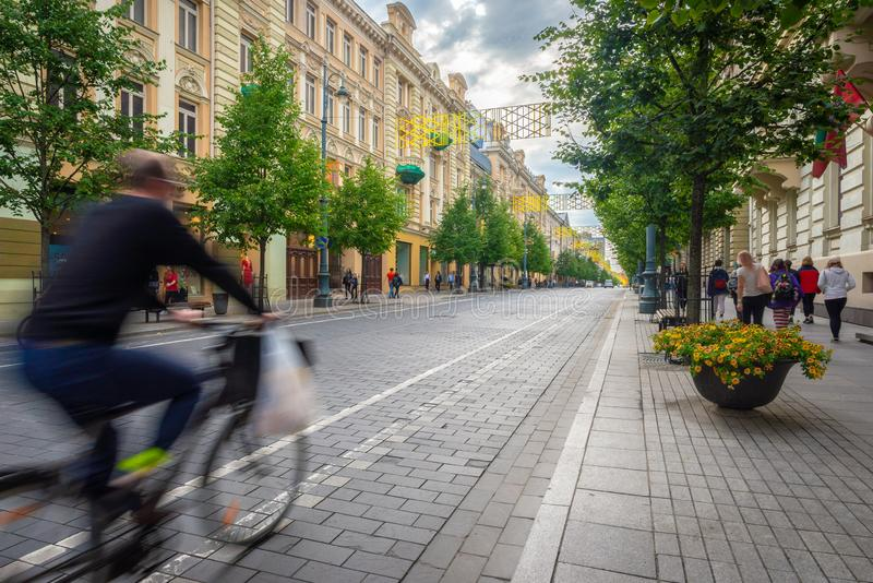 Cyclist swiftly passing by on the main commercial street of Vilnius stock photography