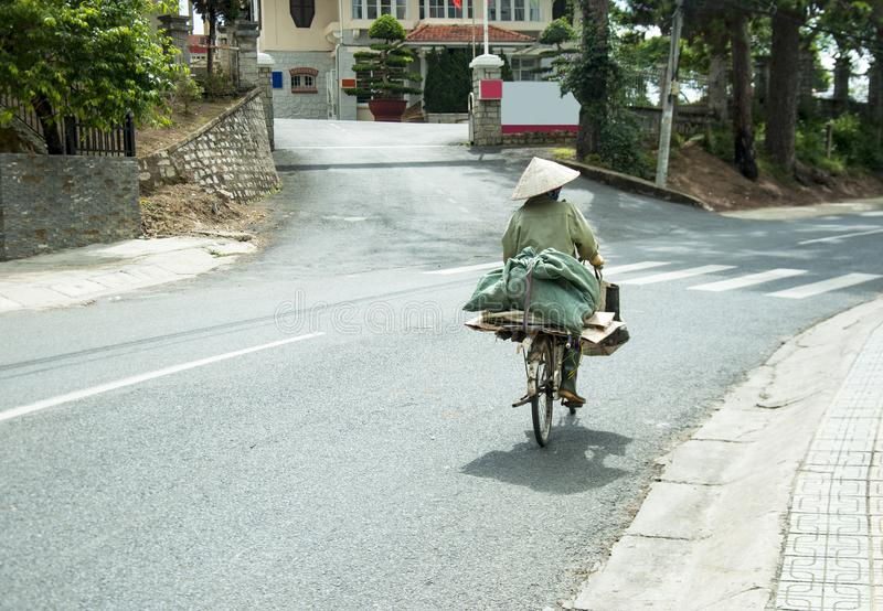 A cyclist in Vietnam carrying a big package of green color stock photography
