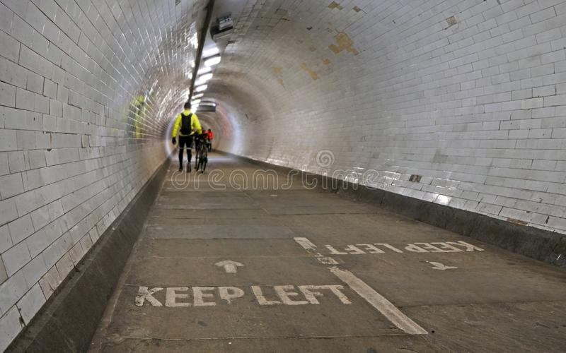 Cyclist wearing yellow jacket walking with his bicycle inside Greenwich foot tunnel under river Thames, more blurred royalty free stock photo
