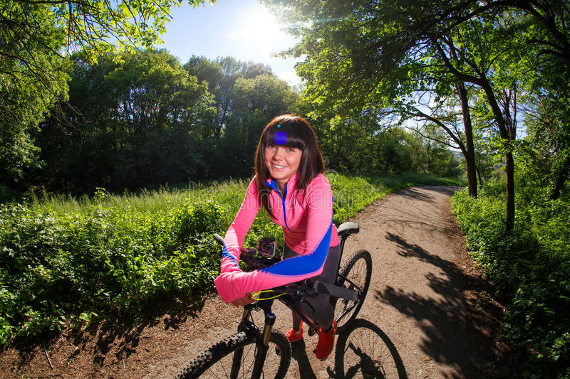 Cyclist woman riding a bicycle in park royalty free stock image
