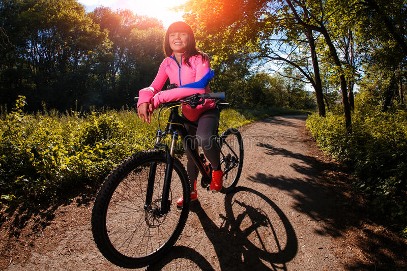Cyclist woman riding a bicycle in park royalty free stock photos