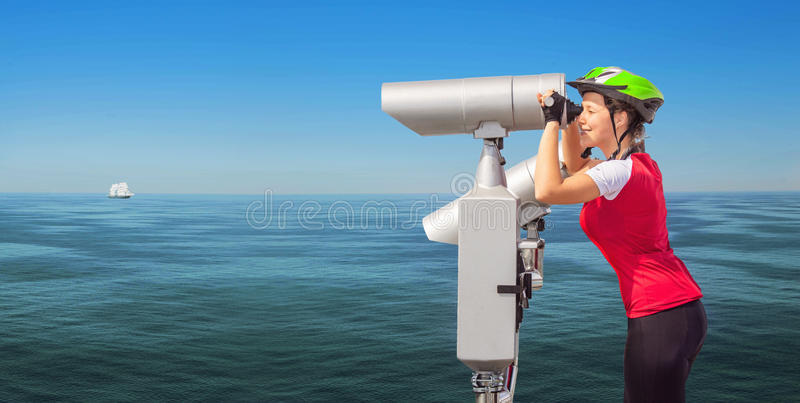 Cyclist woman watching to the sea through a telescope royalty free stock photos