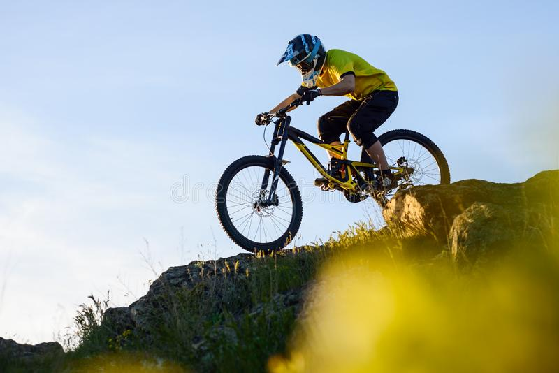Cyclist in Yellow T-shirt and Helmet Riding Mountain Bike Down Rocky Hill. Extreme Sport Concept. stock photo
