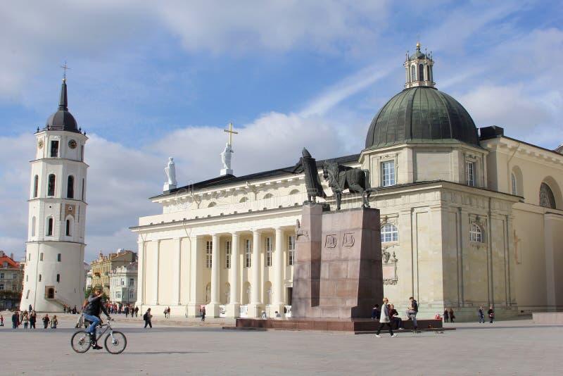 Cycliste à une place avec la basilique de cathédrale et tour de Bell à Vilnius, Lithuanie photographie stock