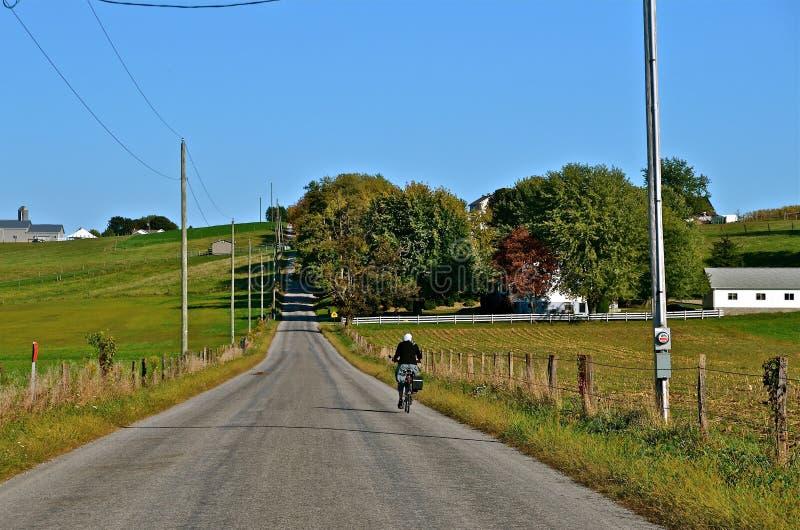 Cycliste amish sur la route image stock