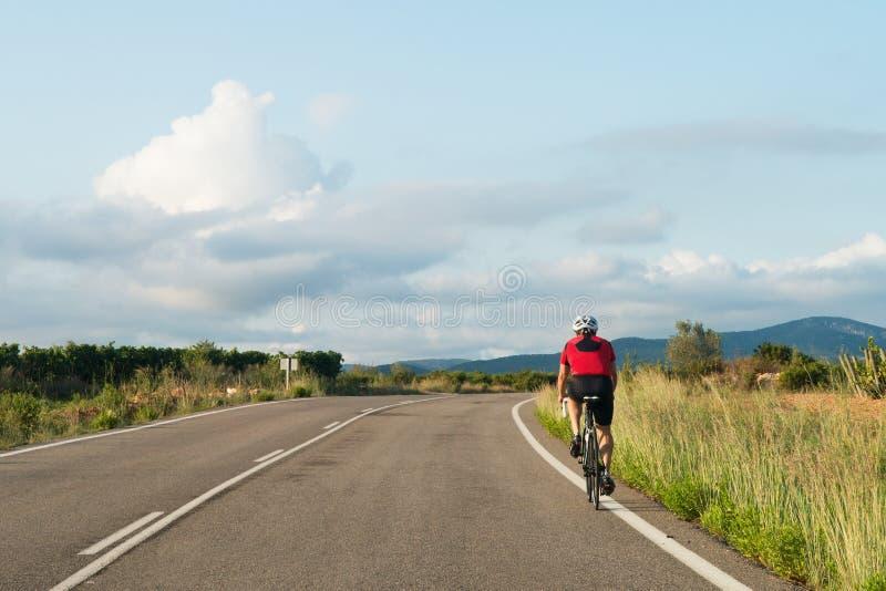 Cycliste dans la route vue de la voiture image libre de droits