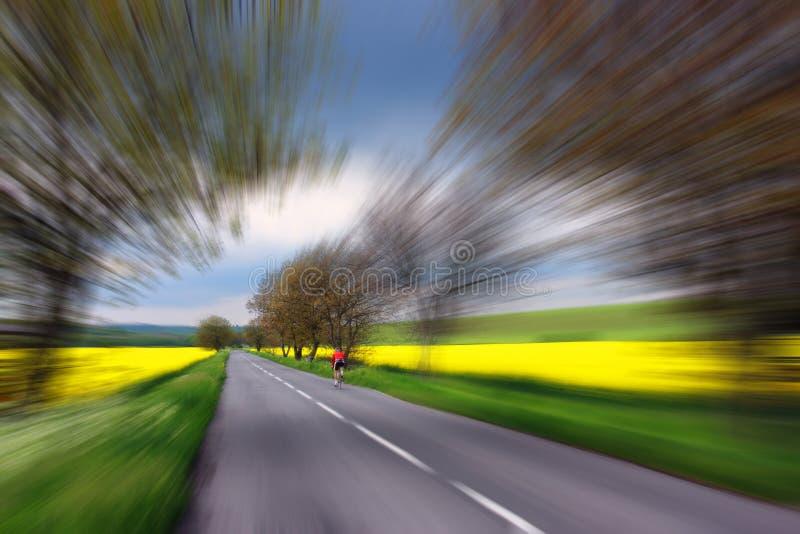 Cycliste dans piloter rouge sur la route rurale images libres de droits