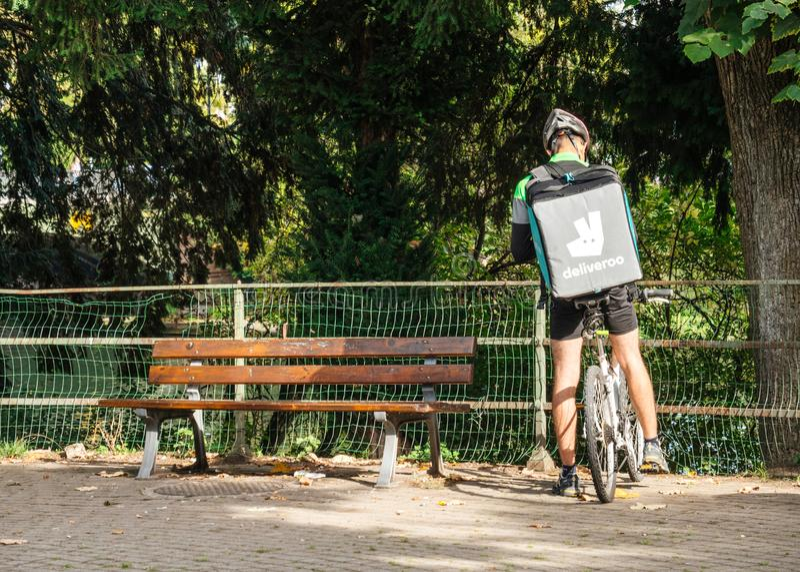 Cycliste de Deliveroo de la livraison de nourriture faisant une pause photo libre de droits