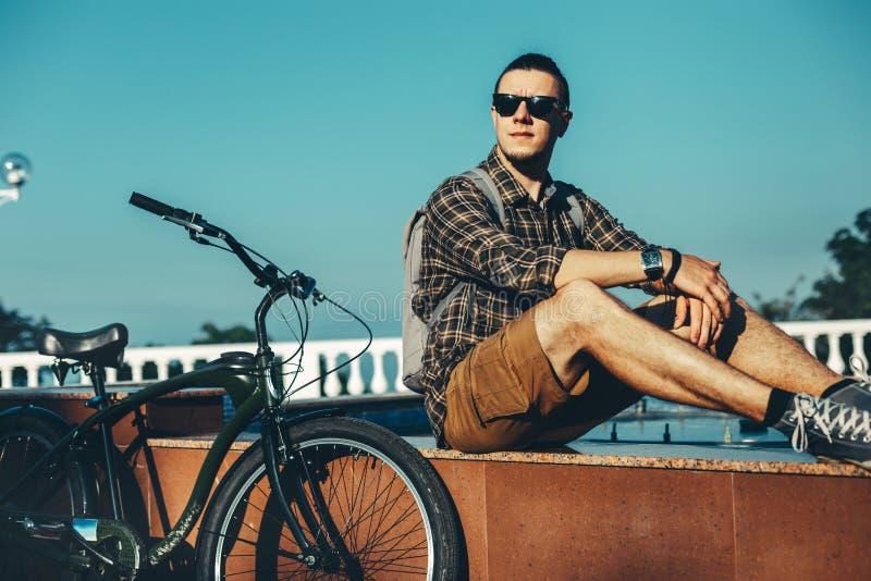 Cycliste de jeune homme s'asseyant sur la fontaine à côté de la bicyclette dans le concept de repos urbain de mode de vie quotidi image stock
