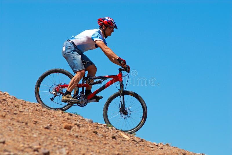 Cycliste de montagne incliné images stock