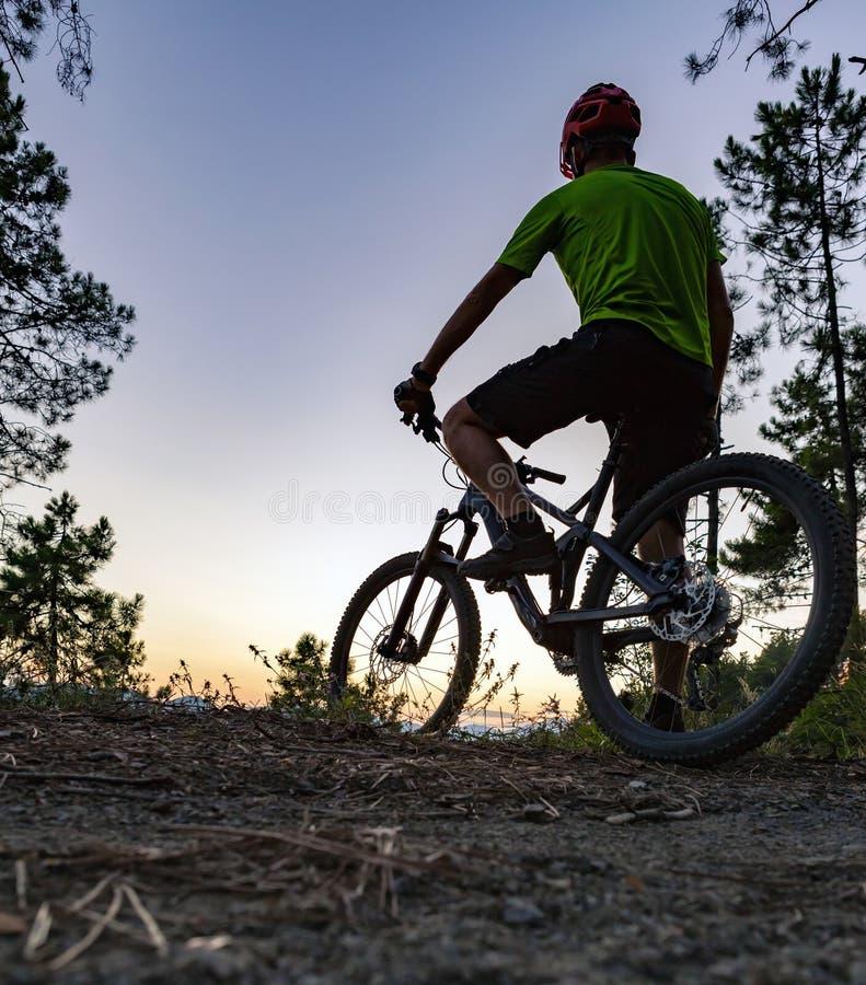 Cycliste de montagne regardant le coucher du soleil, traînée de vélo en montagnes d'automne images stock