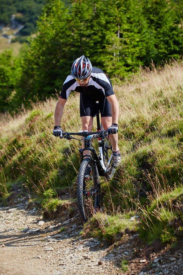 Cycliste de montagne sur des traînées images stock