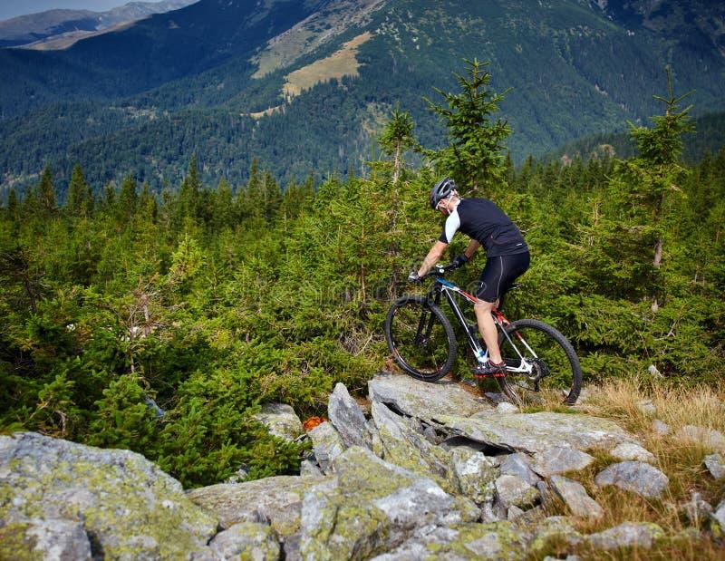 Cycliste de montagne sur des traînées images libres de droits