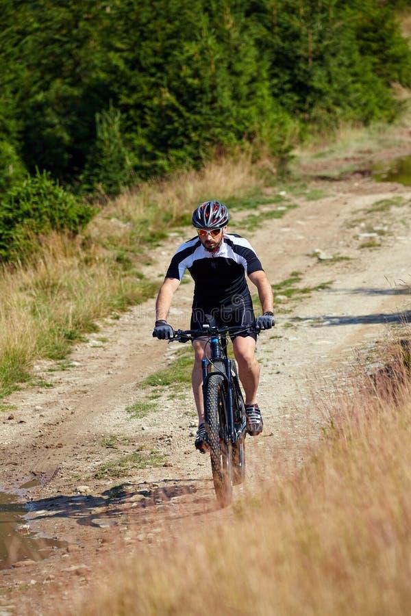 Cycliste de montagne sur des traînées image stock