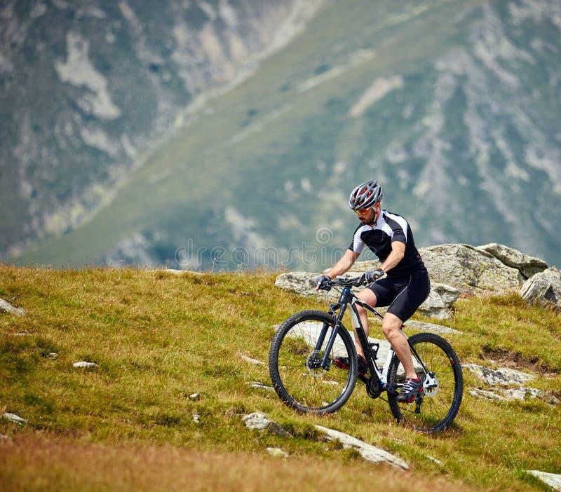 Cycliste de montagne sur des traînées photographie stock