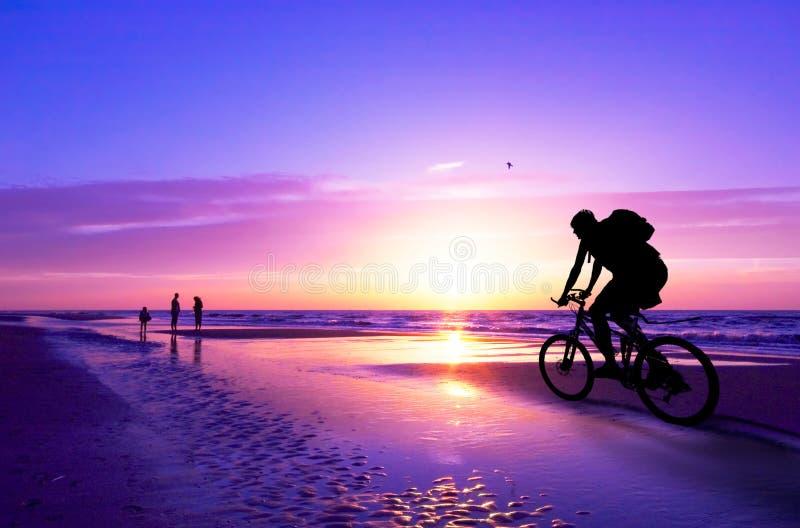 Cycliste de montagne sur la plage et le su image libre de droits