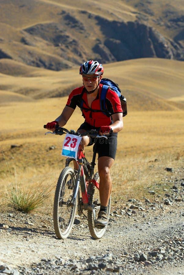 Cycliste de montagne sur le chemin de désert photo stock