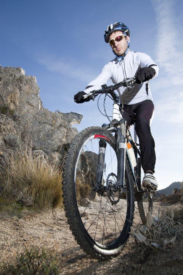 Cycliste de montagne sur le journal photos stock