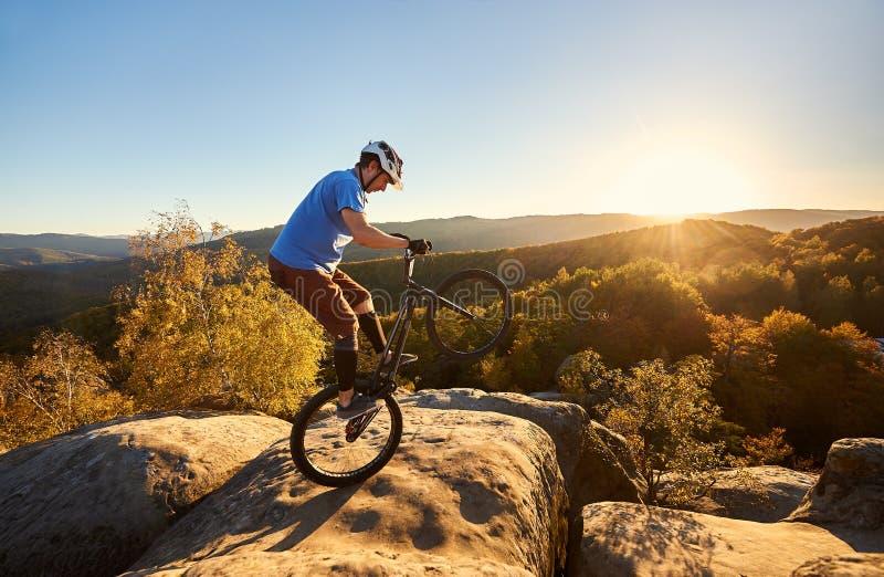 Cycliste de sportif équilibrant sur la roue arrière sur la bicyclette d'essai photographie stock libre de droits