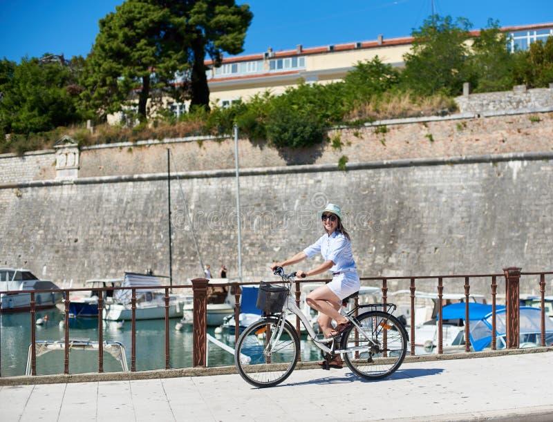 Cycliste de touristes de jeune femme avec la bicyclette de ville dans la ville pr?s de la mer image stock