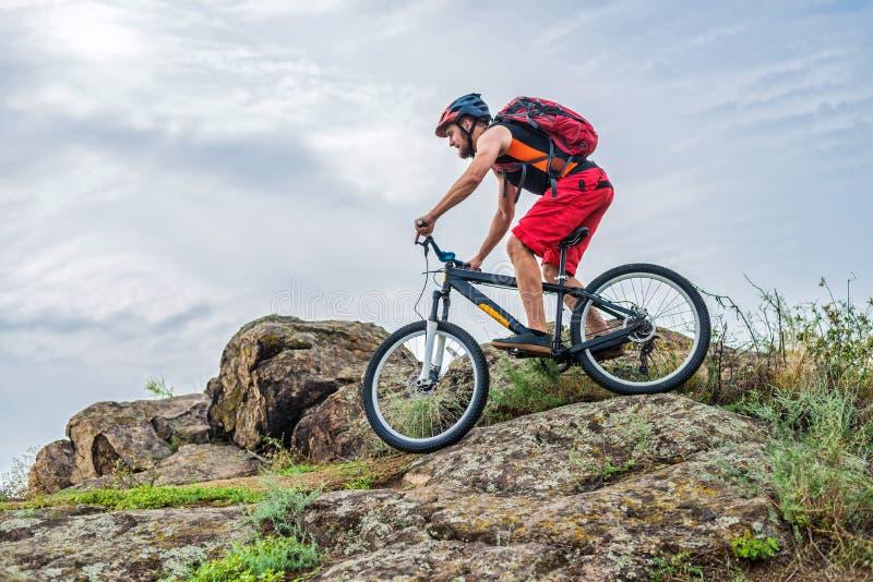 Cycliste descendant en bas de la roche sur un vélo de montagne, un mode de vie actif photos libres de droits