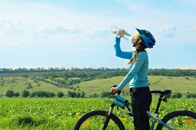 Cycliste féminin, bouteille d'eau potable image libre de droits