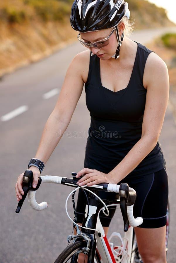 Cycliste féminin vérifiant le temps photos libres de droits