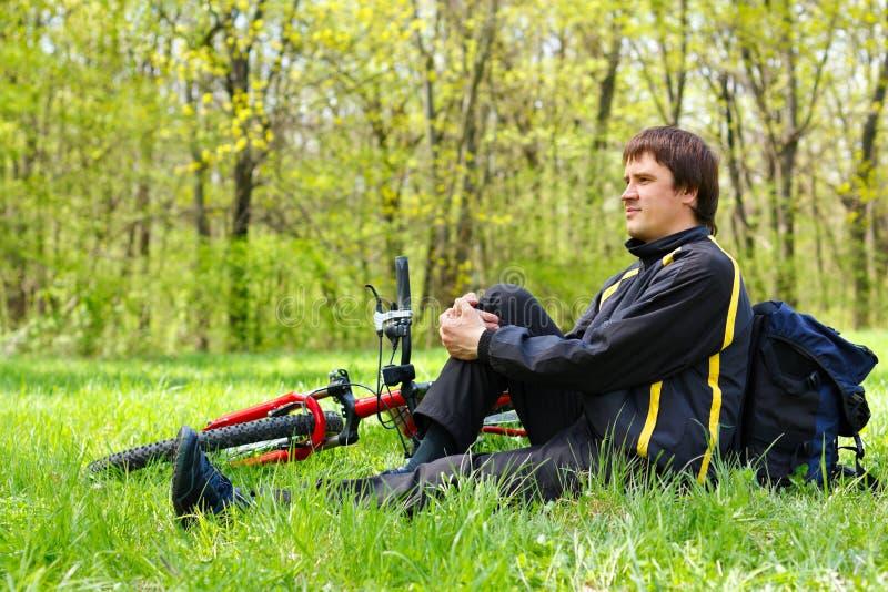 Cycliste heureux d'homme avec le vélo se reposant sur l'herbe verte image stock