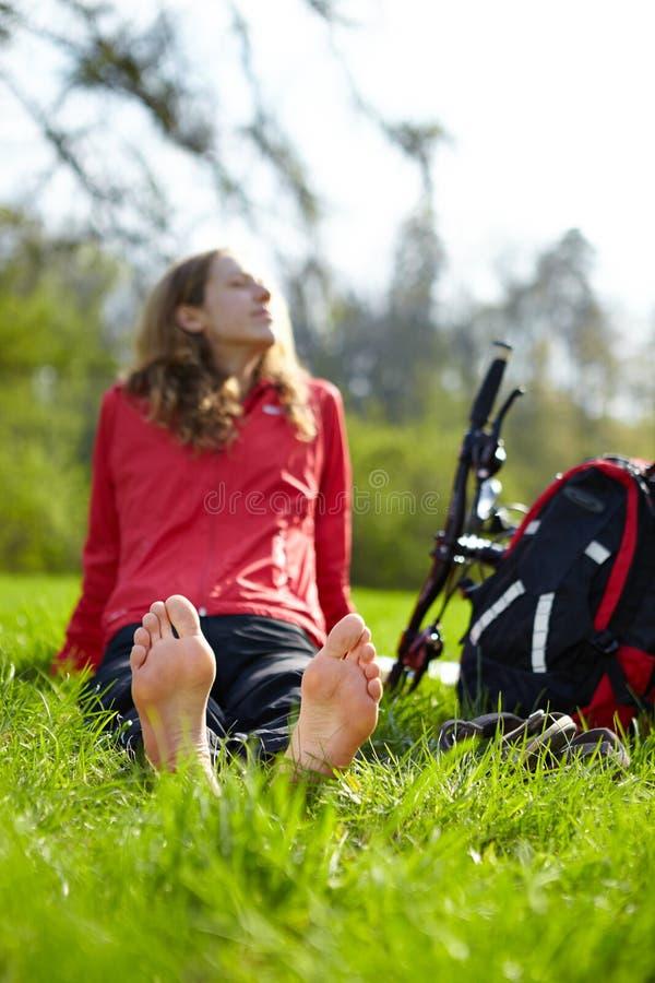 Cycliste heureux de fille appréciant la relaxation se reposant nu-pieds dans l'herbe verte photographie stock