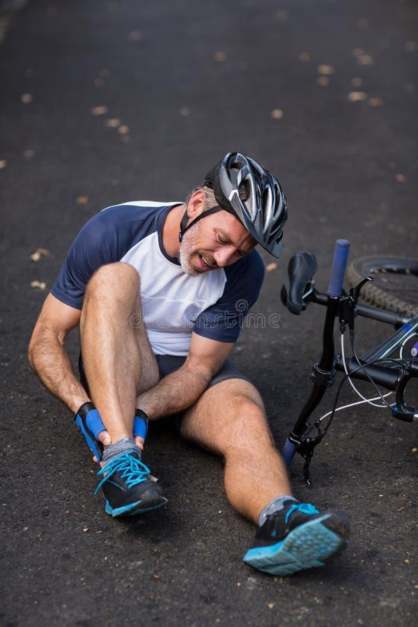 Cycliste masculin en douleur tenant sa jambe blessée photographie stock libre de droits