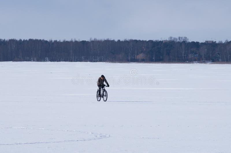 Cycliste masculin non identifié montant un vélo pendant l'hiver sur le lac congelé photo stock