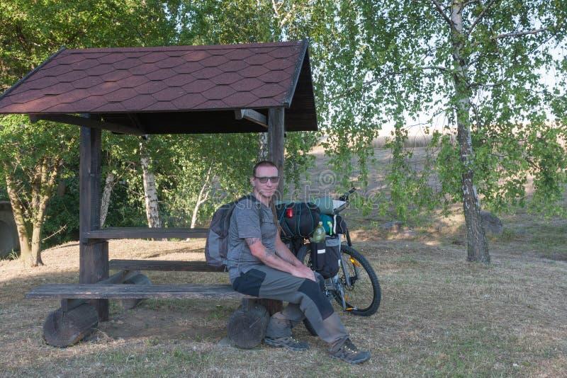 Cycliste s'asseyant sur un banc sous le gazepo image stock