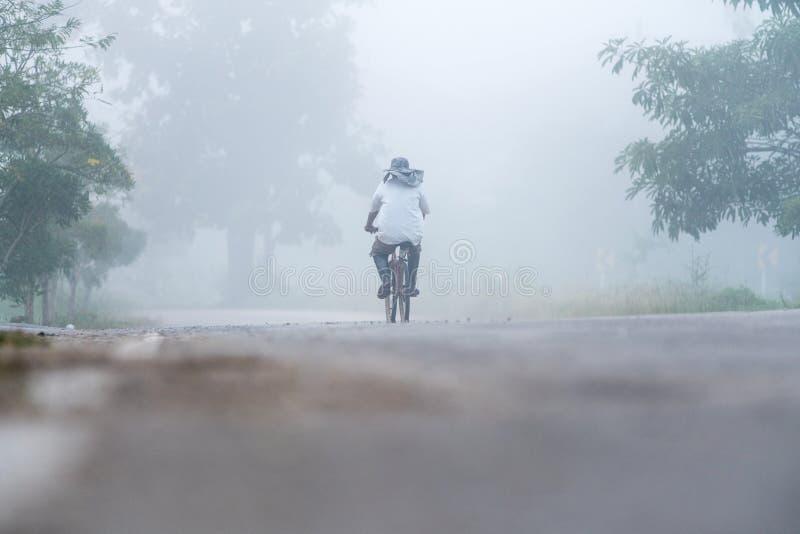 Cycliste seul dans le brouillard image stock