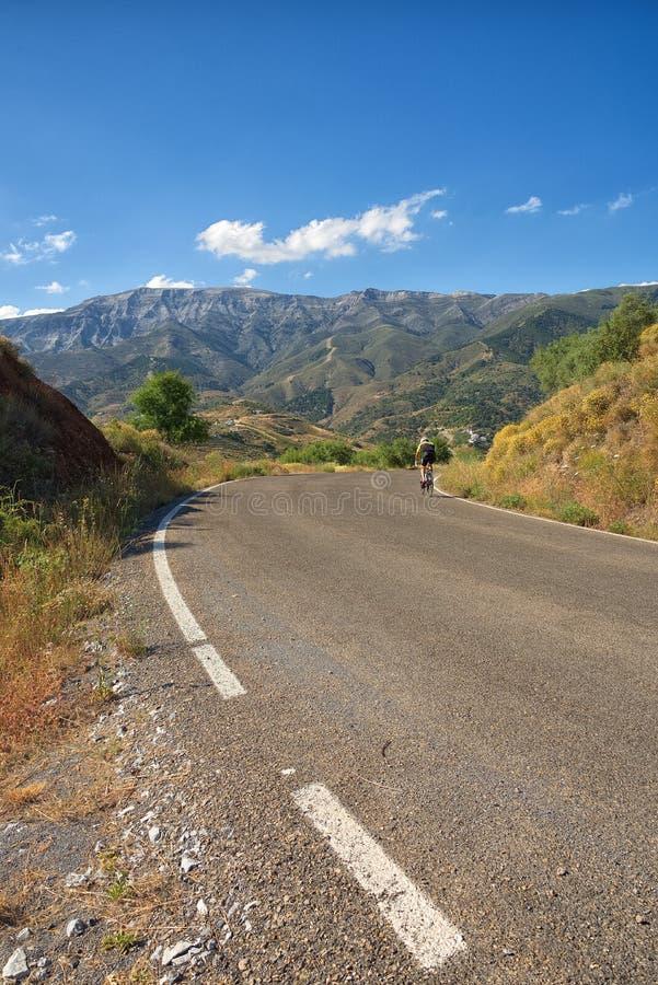 Cycliste solitaire, se dirigeant vers une courbure dans la route Andalousie, Espagne photos stock
