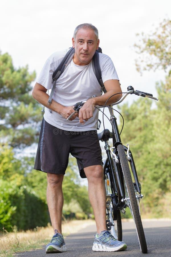 Cycliste supérieur appréciant la nature et faisant la pause photo stock