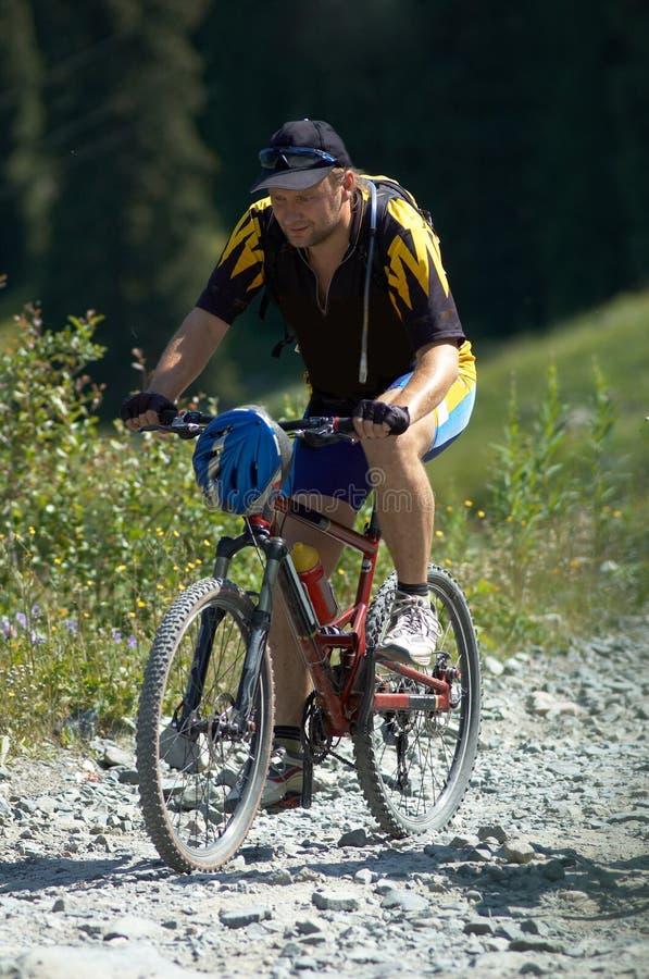 Cycliste sur la route de montagne photos stock