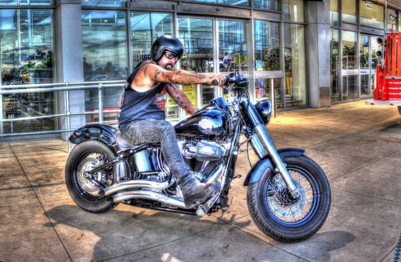 Cycliste tatoué sur la motocyclette de Harley Davidson photo stock