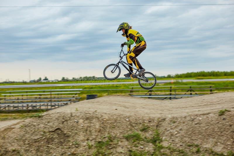 Cycliste tous terrains professionnel sautant sur la bicyclette image stock