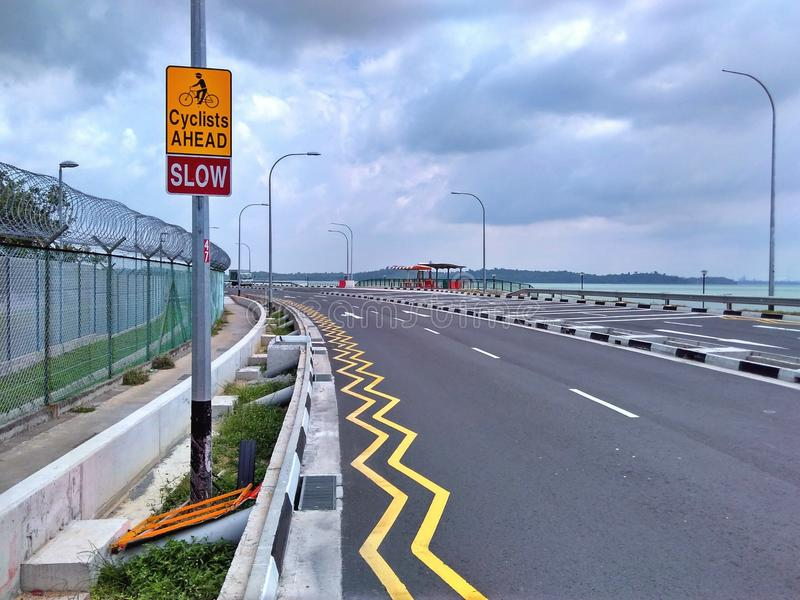 'Cyclists ahead' sign. To warn motorists to keep a lookout for people cycling along Changi Coastal Road in Singapore royalty free stock photo