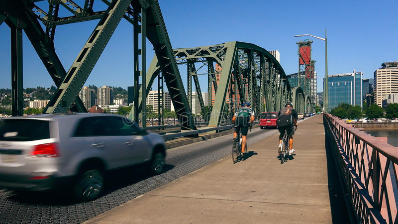 Cyclists and Cars Cross the Hawthorne Bridge Into Portland, Ore. Cyclists and automobiles cross the Hawthorne Bridge heading into Portland, Oregon stock photos