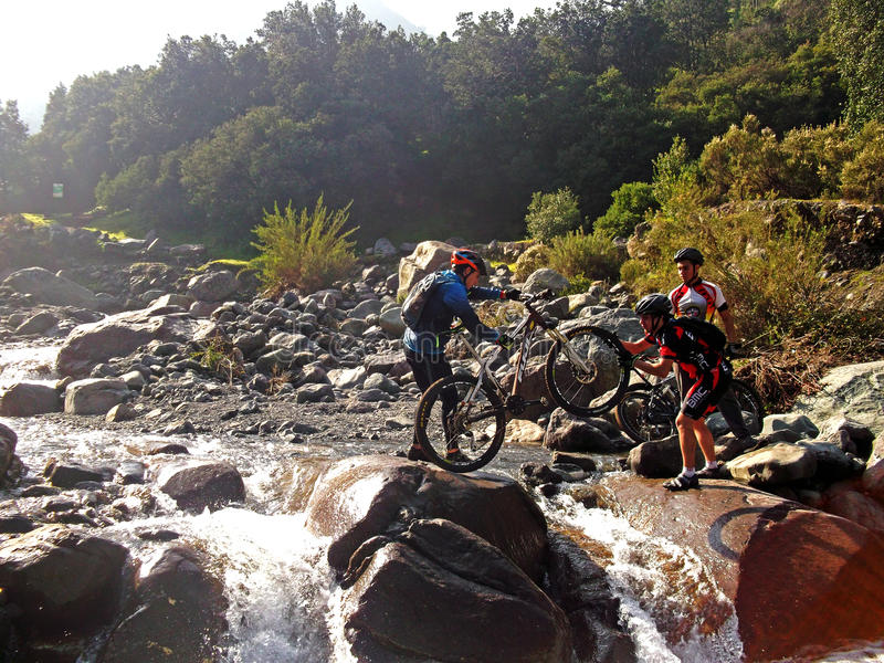 Cyclists crossing a river royalty free stock photography