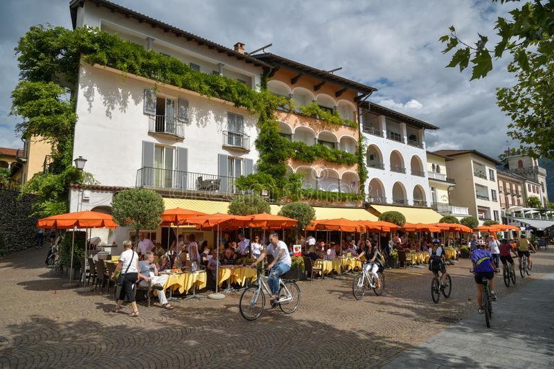 Cyclists driving next to open restaurant on the promenade in Ascona, Switzerland. Ascona, Switzerland - September 2, 2018: Cyclists driving next to open stock images