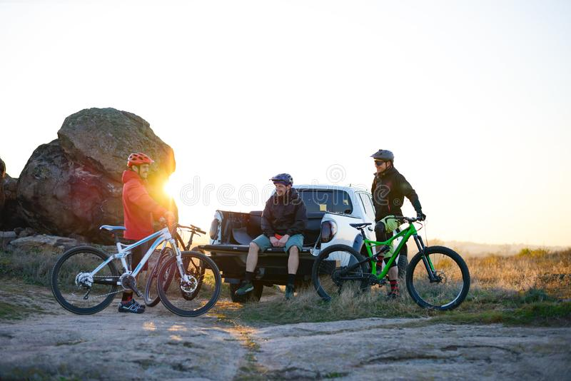 Friends are Resting on Pickup Offroad Truck after Bike Riding in the Mountains at Sunset. Adventure and Travel Concept. Cyclists Friends are Resting on the stock images