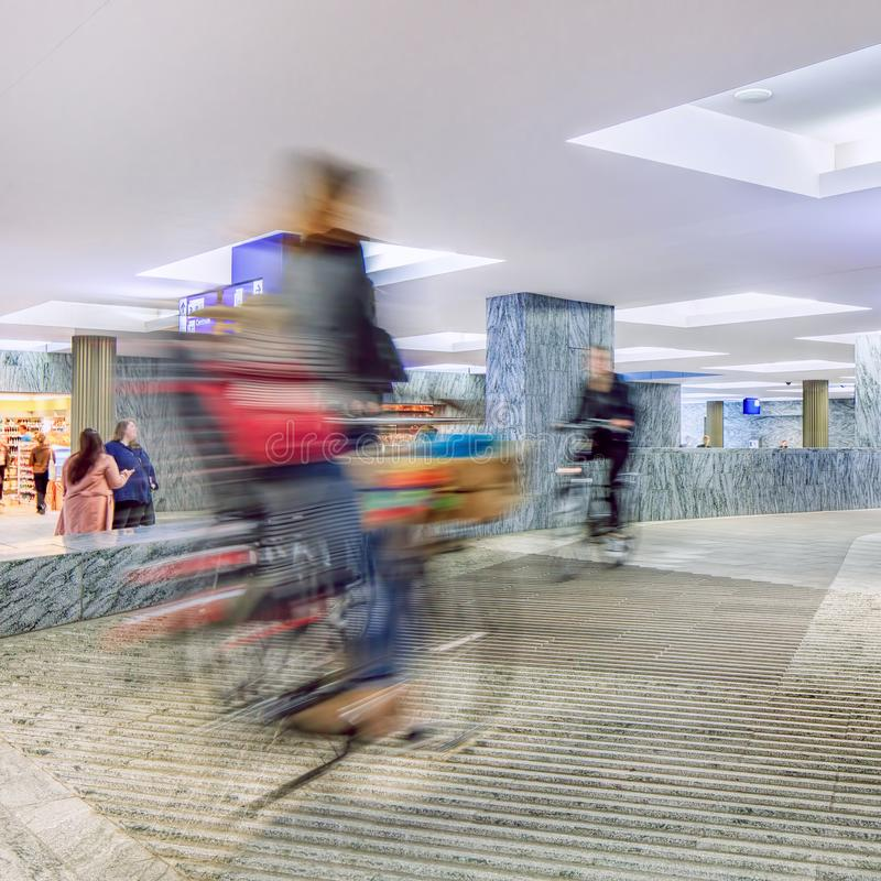 Cyclists on an indoor cycle lane of a modern station, Breda, Netherlands. Cyclists with motion blur on an indoor cycle lane of a modern station, Breda stock image