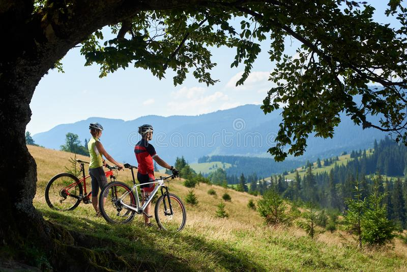 Cyclists, man and woman in helmets and full equipment, standing with bikes on grassy hill. Young couple male and female riders in helmets and full equipment royalty free stock photo