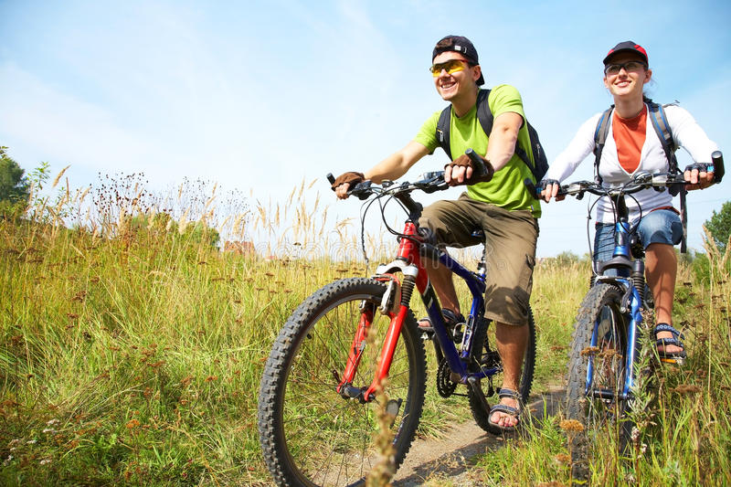Cyclists on meadow stock images