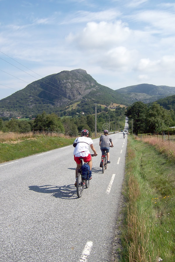 Cyclists in Norway. A group of cyclists riding along an asphalt road, characteristic Norwegian sights, a mountain in the background. Norway county stock images